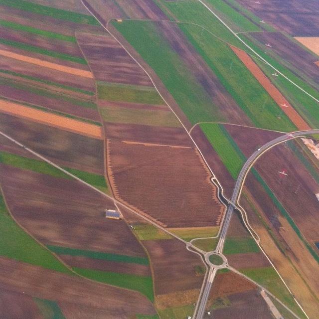 Ein Kreisverkehr inmitten von Äckern nebst einer Hochspannungsleitung und einem frisch gedüngten Feld