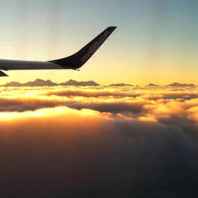 Morgenflug über den Wolken mit Bergketten im Hintergrund