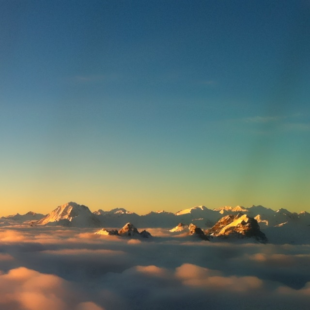 Morgenflug bei Sonnenaufgang mit Bergen über der Wolkendecke