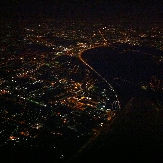 Nachtflug über einer hell erleuchteten Stadt