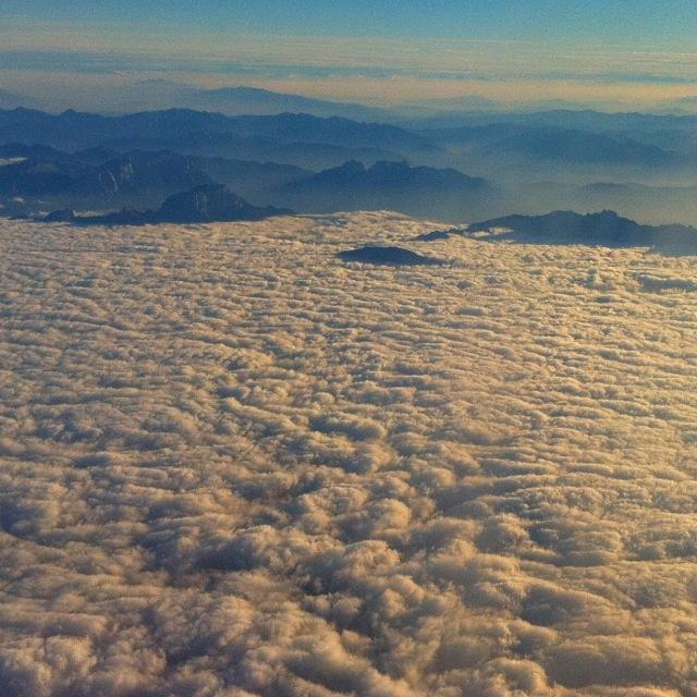 Wolken die bis zu den Bergen im Hintergrund reichen