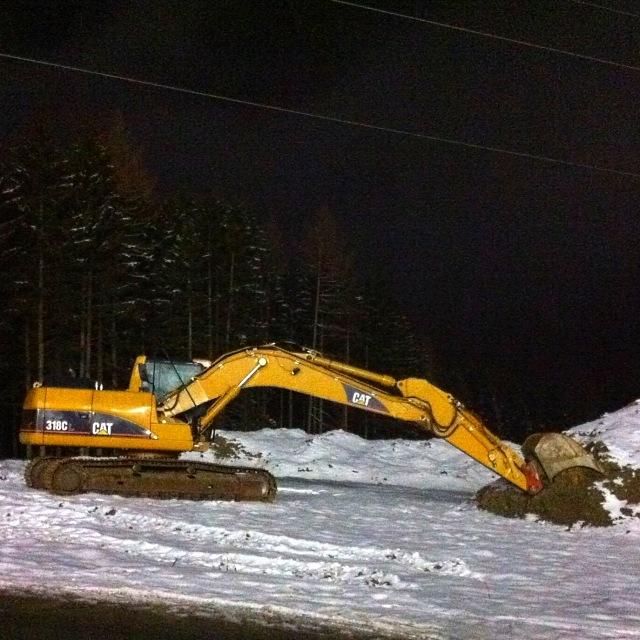 Caterpillar nachts im Schnee, erhellt von der Skipistenbeleuchtung
