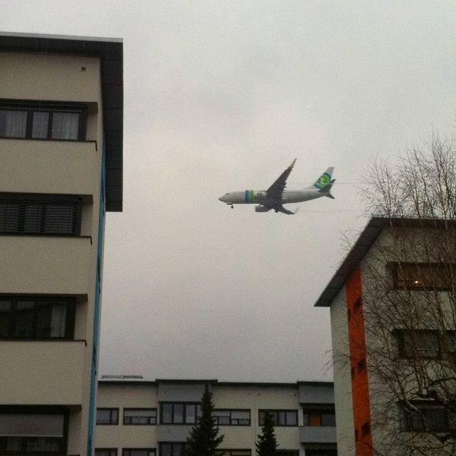 Flugzeug beim Landeanflug, knapp über den Dächern