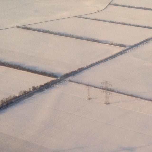 Monochrome Winterlandschaft mit Hochspannungsmasten