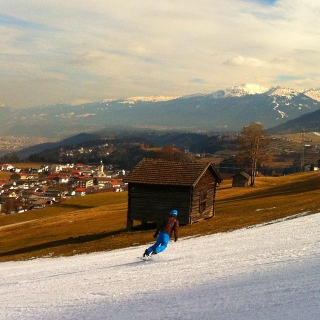 Snowboarder auf einem Schneestreifen neben der grünen Wiese