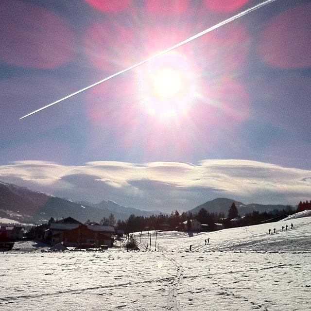 Föhnwolken, Sonne, Schnee und ein Flugzeug mit Kondensstreifen